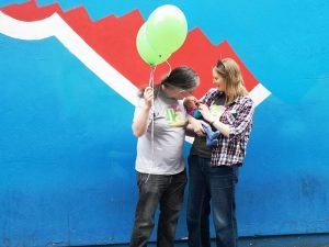 Photograph of Helen Stonehouse, her partner and baby, with balloons ,in front of the partial Repeal mural.