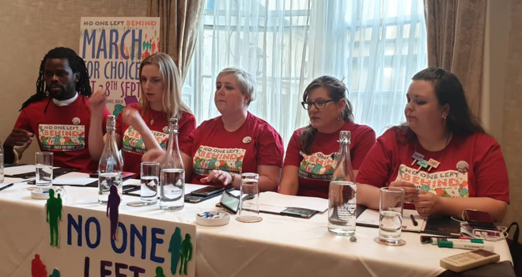 Panel from today's March for Choice press conference. Five people seated behind a long table, all wearing red march for choice tshirts. Pictured are  Bulelani Mfaco (MASI),   Steph Hanlon (Carlow Choice and Equality Network), Linda Kavanagh (ARC), Mara Clarke from Abortion Support Network (ASN), Danielle Roberts (Alliance for Choice Belfast)