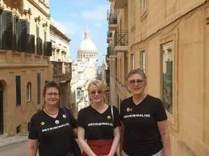 Photograph of three members of Leitrim ARC on a street in Malta, dressed in black 'Decriminalise' tshirts