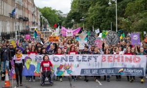 "Photograph of crowd gathered at March for Choice 2019. Banner reads ""No one left behind"", extending across bottom of photo. ARC members in red tshirts are to the front with a crowd behind them carrying a variety of signs and banners."