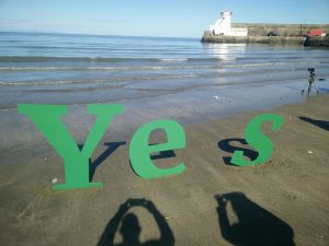 """Lettering """"Y e s"""" pictured on a beach"""