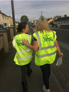 Two canvassers walk down a street with their backs to camera, wearing together for yes high vis vest. One has her arm on the other's back
