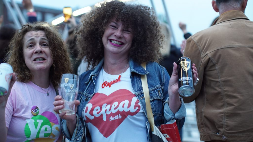 Two women pictured outside a bar in repeal tshirts, badges and necklaces