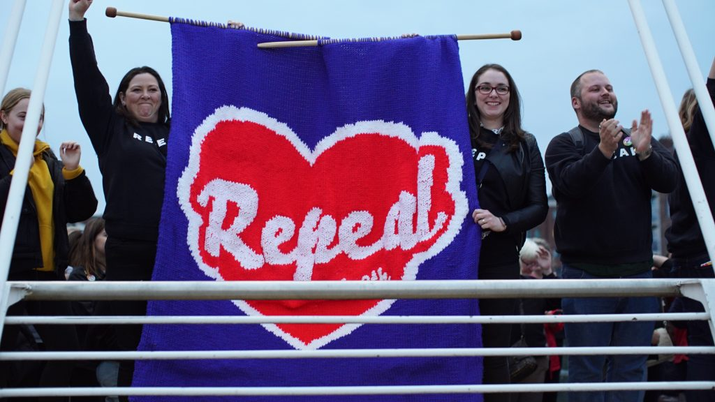 A group of people pictured on a bridge, two are holding a large knitted Repeal (maser) logo