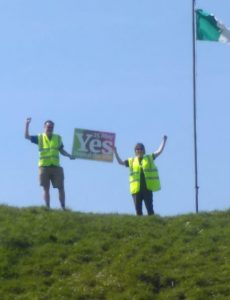 Two volunteers (including Clare) holding a Together for Yes placard on a hilltop