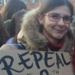Image of Joanne Kompa holding a cardboard sign that reads 'Repeal the 8th'