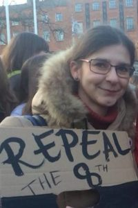 Photography of Joanne Kompa holding a cardboard sign that reads 'Repeal the 8th'